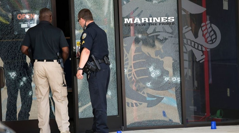 Police officers enter the Armed Forces Career Center through a bullet-riddled door after a gunman opened fire on the building, July 16, 2015, in Chattanooga, Tenn. (Photo: Associated Press)