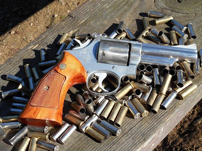 sw model 66 revolver on top of empty bullet casings