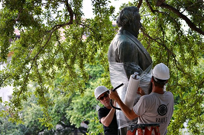 Workers from Vault Fine Art Services prepare to remove the Jefferson Davis statue from the Main Mall on Sunday morning. The work crew also removed the statue of Woodrow Wilson. (Photo: Charlotte Carpenter / The Daily Texan)