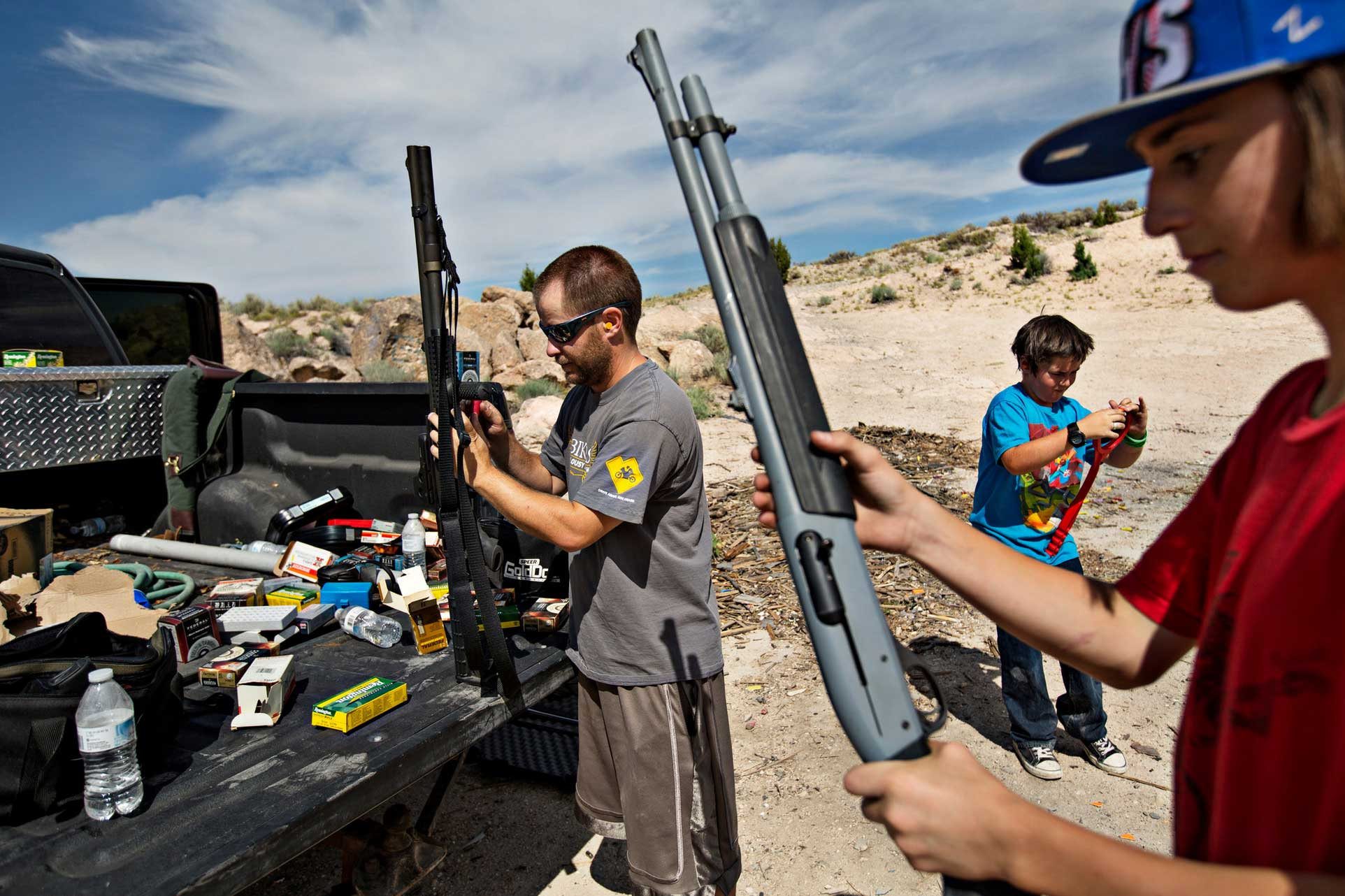 Dave Joseph, left, and his son, Casey, right, loaded guns for target shooting this month on land owned by the Utah School and Institutional Trust Lands Administration. (Photo: New York Times)