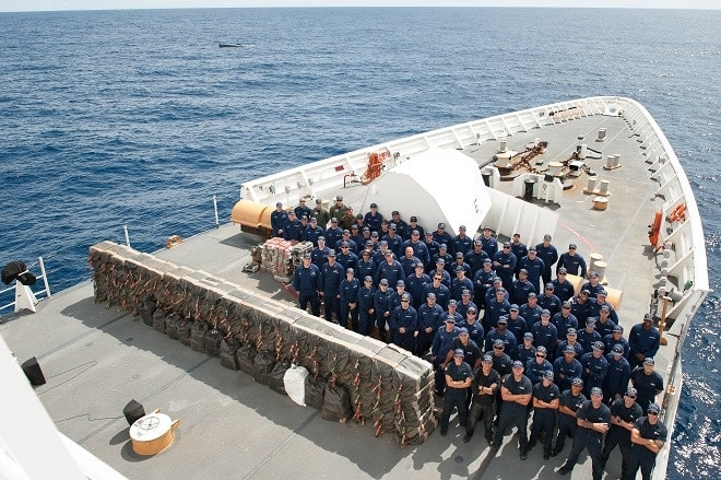The Coast Guard Cutter Stratton crew is shown with cocaine bales seized from a self-propelled semi-submersible interdicted in international waters off the coast of Central America, July 19, 2015. The Coast Guard recovered more than 6 tons of cocaine from the 40-foot vessel. (Coast Guard photo courtesy of Petty Officer 2nd Class LaNola Stone)