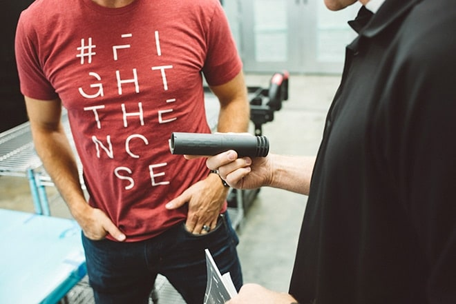 Denning-inspecting-a-can-SilencerCo-co-owner-Josh-Waldron-in-the-background-sporting-a-Fight-The-Noise-shirt