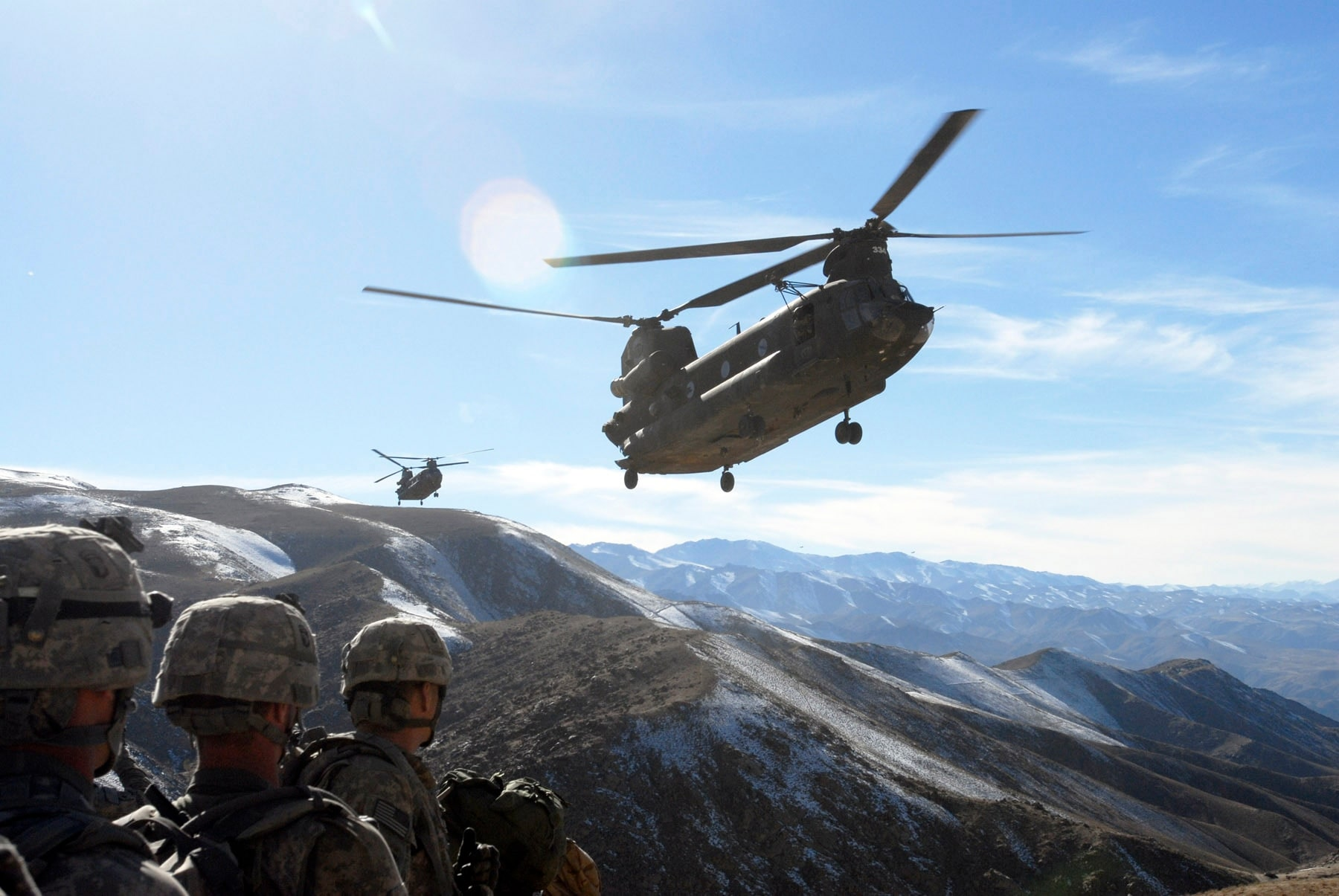 Standing by on a hill top, Soldiers with the 101st Division Special Troops Battalion, 101st Airborne Division watch as two Chinook helicopters fly in to take them back to Bagram Air Field, Afghanistan Nov. 4, 2008.  The Soldiers searched a small village in the valley below for IED making materials and facilities. (Photo by Spc. Mary L. Gonzalez, CJTF-101 Public Affairs)