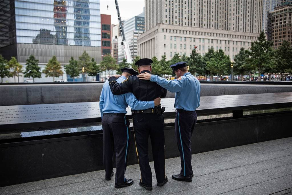 Mitch Ellicott, a lieutenant with the Sussex County Sherriff's office, is flanked by his sons Zachary, left, and Benjamin, both firefighters in Stanhope, New Jersey, take a moment to remember a family member lost in the attacks of September 11, 2001, on the 14th anniversary of the attacks. (Photo: Getty Images)