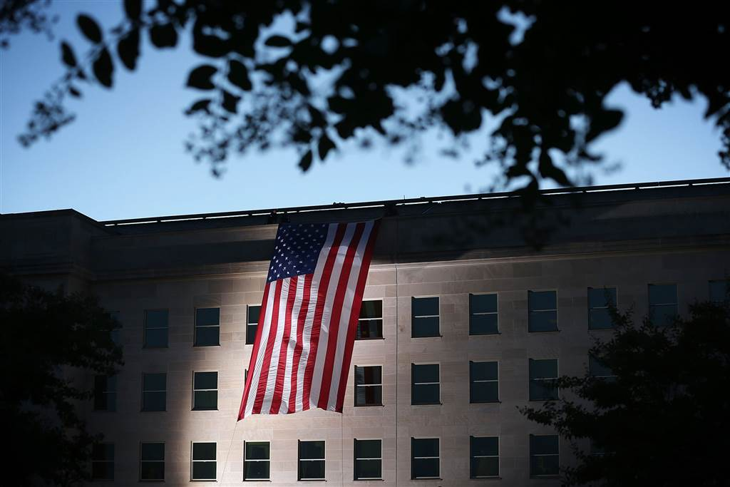 Pentagon personnel unfurl a large American flag on the west side of the Pentagon on Sept. 11 in Arlington, Virginia. (Photo: Getty Images)