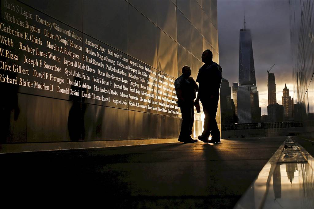 People read the names of victims at the 9/11 Empty Sky memorial at sunrise across from New York's Lower Manhattan and One World Trade Center in Liberty State Park in Jersey City, New Jersey, on Sept. 11. (Photo: Reuters)