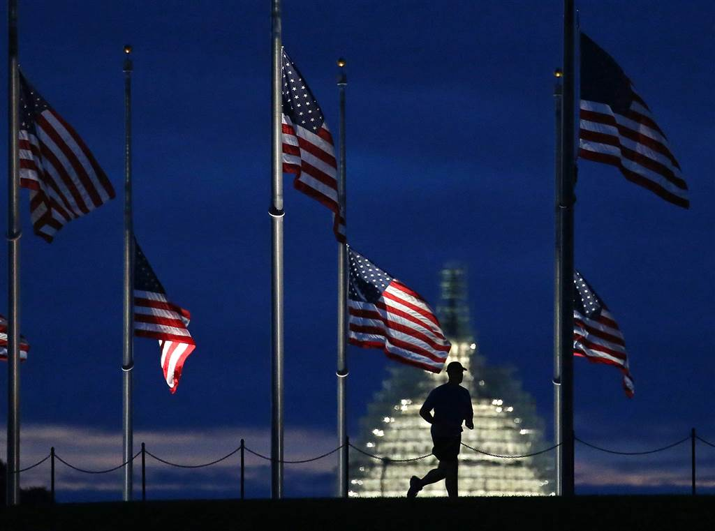 A man jogs past a row of American flags that have been lowered to half staff on the Washington Monument grounds early on Sept. 11.  (Photo: Getty Images)