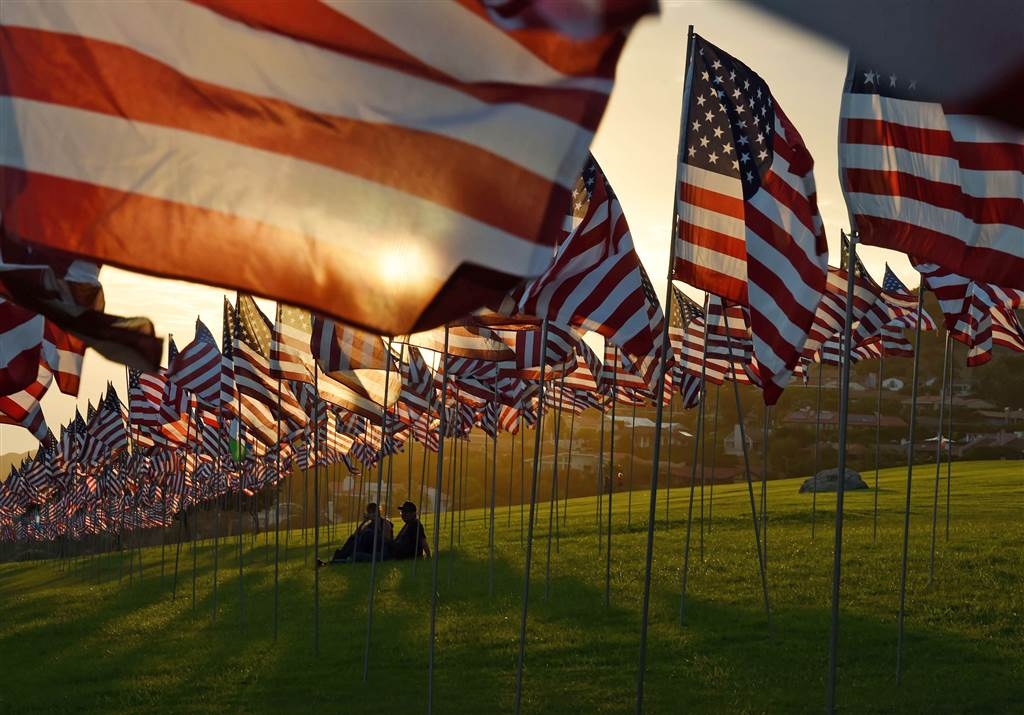 People sit among U.S. flags erected by students and staff from Pepperdine University to honor the victims of the Sept. 11, 2001 attacks at their campus in Malibu, California, on Sept. 10. The students placed some 3,000 flags in the ground in tribute to the nearly 3,000 victims lost in the attacks 14 years ago. (Photo: Getty Images)