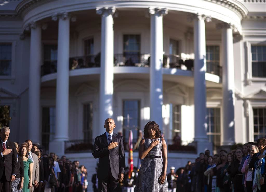 President Obama and first lady Michelle Obama observe a moment of silence on the South Lawn of the White House to mark the anniversary of the attacks. (Photo: Getty Images)