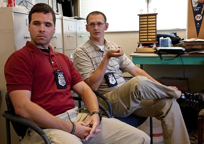 In this Sept. 9, 2009 photo, Milwaukee police officer Bryan Norberg, right, and Officer Graham Kunisch talk in their captain's office in Milwaukee. Norberg and Kunisch were both shot on June 9, 2009, by Julius Burton. (AP Photo/Morry Gash)