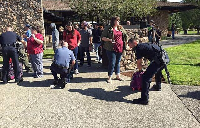 Authorities search bags as students evacuate Umpqua Community College.