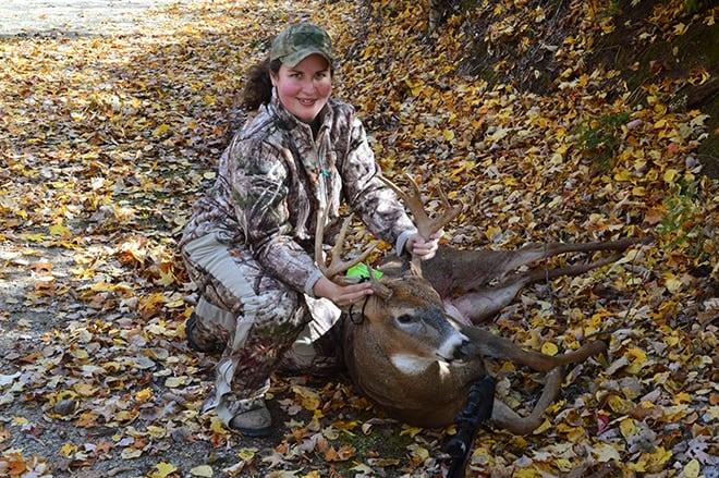 female hunter posing with trophy deer