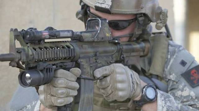 A soldier pointing a rifle equipped with an EOTech scope.