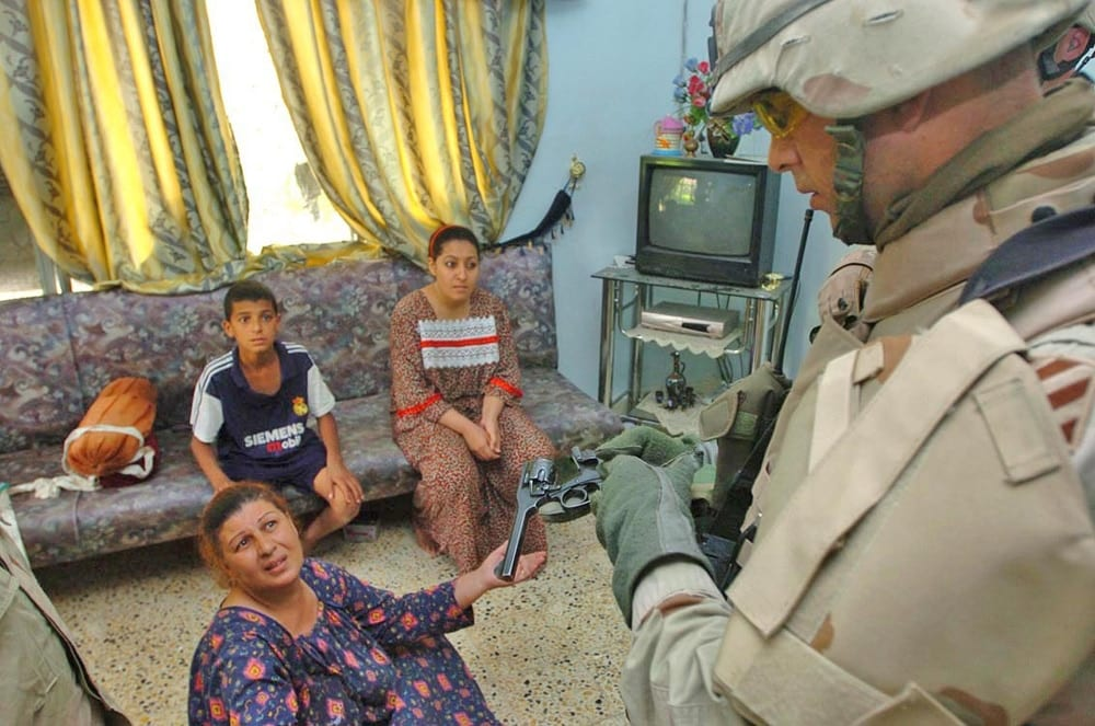 Capt. Dustin Baadte, C Co., 1-64 Armor, commander, asks a woman about a .38 caliber pistol found in her home during a raid in New Baghdad, Iraq, June 6. Civilians need a permit to posess handguns in the Baghdad area.