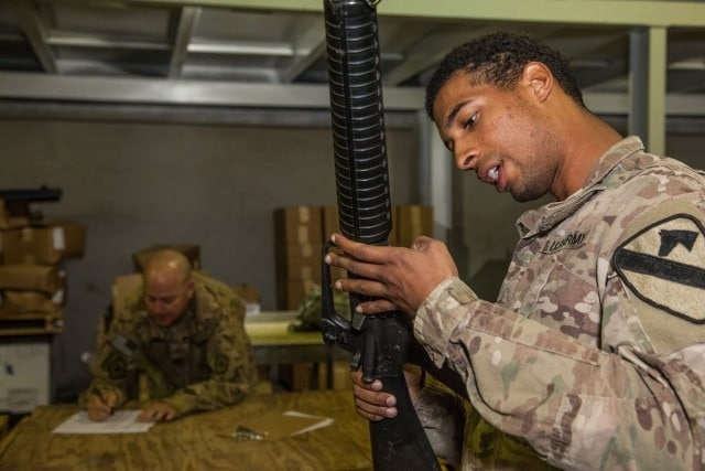 U.S. Army Spc. Daniel Mateo, assigned to 17th Sustainment Brigade, reads the serial number for an M16 rifle during a weapons inventory near Erbil, Iraq, Feb. 22, 2016