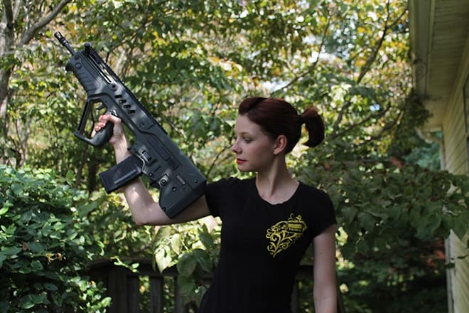 woman holding a tavor sar rifle