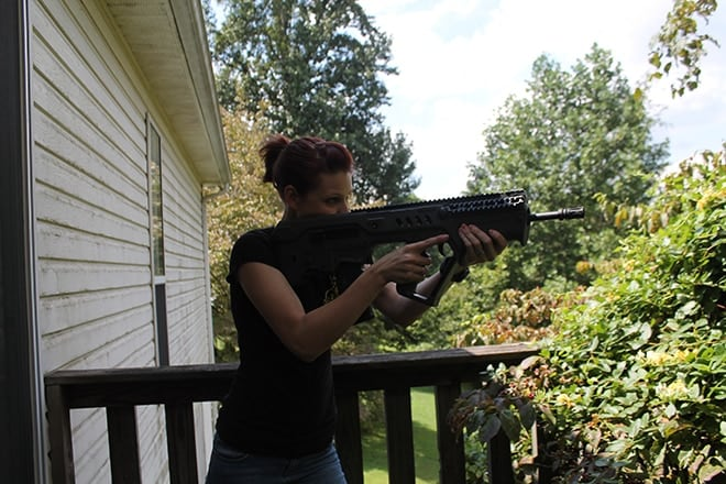 woman in shooting stance with a tavor sar