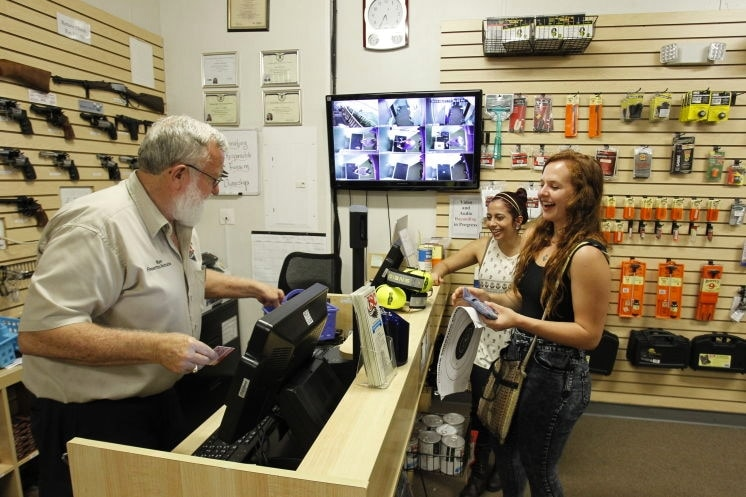 Indoor Shooting owner Ken Zellers chats with Amy Allen and Evangelon James after their recent target practice session at the E Fowler Avenue store in Thonotosassa. He says nearly half of his customers are younger than 40. (Photo: Tampa Bay Times)