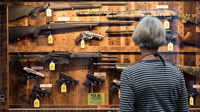 A woman peruses a gun case. (Photo: Bloomberg)
