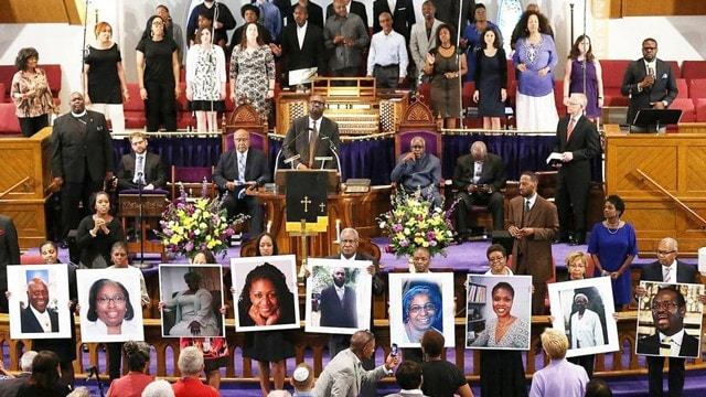 Pictures of the nine people gunned down at the Emanuel AME Church in Charleston were held up by congregants during a prayer vigil at the the Metropolitan AME Church in Washington, D.C. (Photo: Win McNamee/Getty Images)