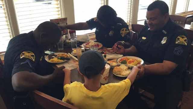 boy prays with cops