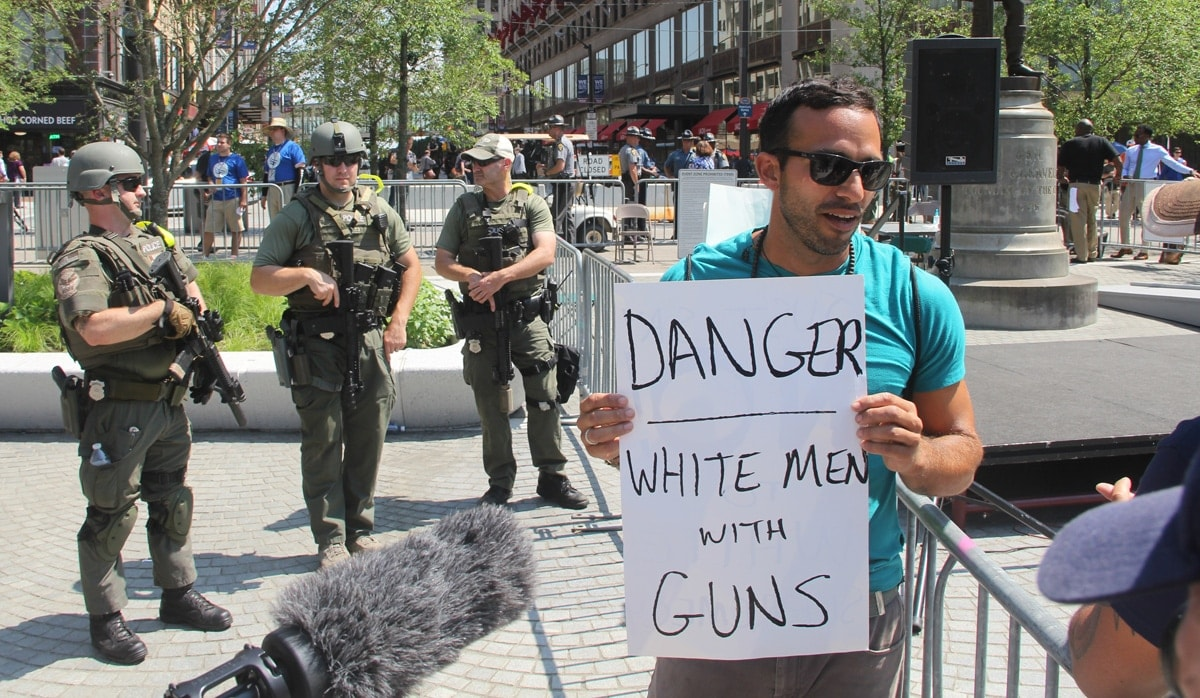 Man with a sign posing with a sign satirizing the officers, who, unlike other officers, wore SWAT gear and carried rifles.