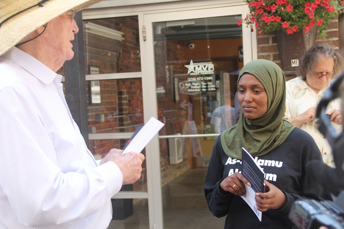 A demonstrator passing out anti-Sharia Law materials speaks to a presumable Muslim woman.