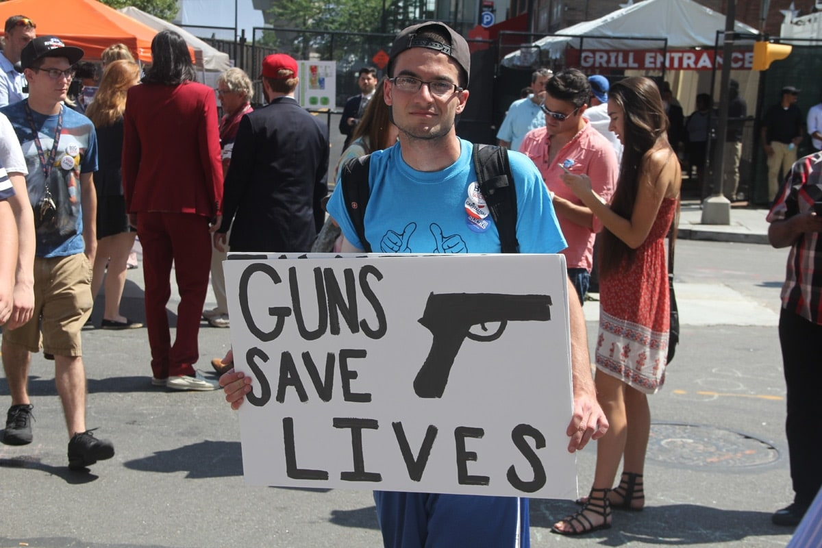 """A man holds a """"guns saves lives"""" sign as he walks around the Quicken Loans Convention Center."""