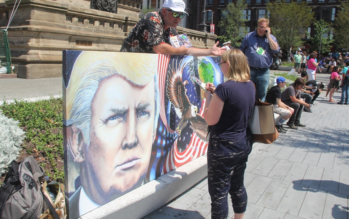 A man walking around with a mural of Donald Trump.