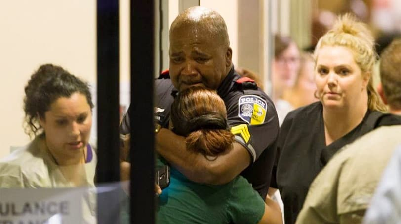 A DART (Dallas Area Rapid Transit) police officer receives comfort at Baylor University Hospital emergency room entrance on July 7, 2016 in Dallas, Texas. (Photo: Associated Press)