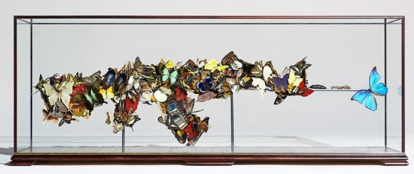 """Beat of a Wing"" is a decommissioned AK-47 covered in real butterflies. Within the magazine there are clear 7.62 empty rounds each holding a commodity which are Symondson's utopian vision of mother nature reclaiming earth from the environmental damage that man has caused: Sugar representing over farming, Dead fish representing the damage to the oceans, Sawdust to represent deforestation etc.(Photo and caption: Maddox Gallery)"