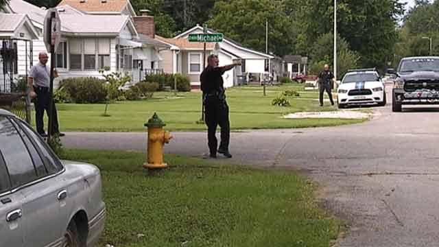 police guiding traffic at crime scene