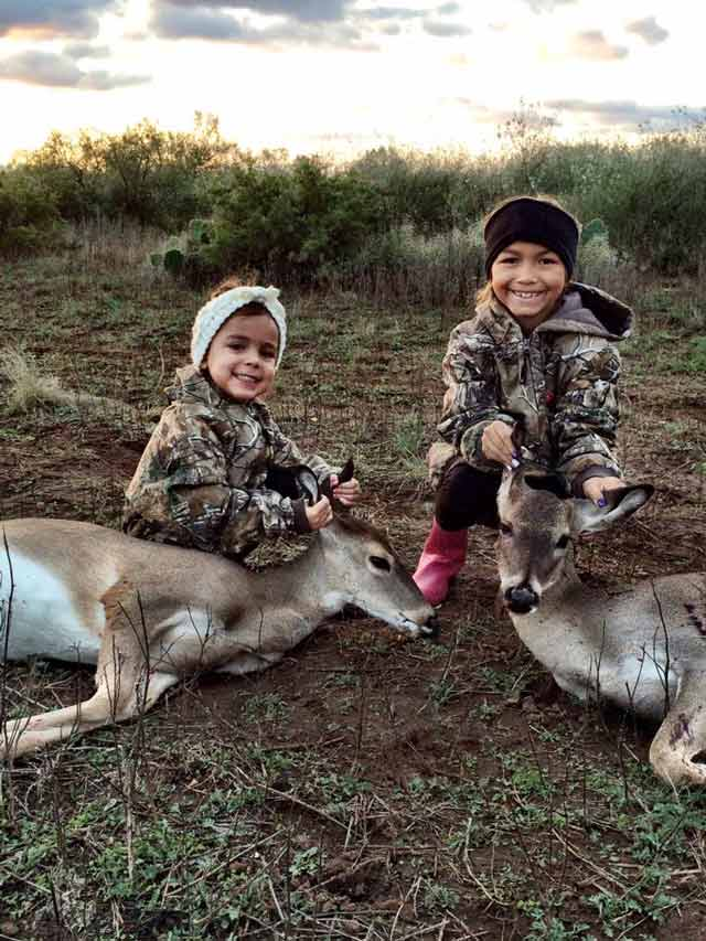 children pose next to hunted deer
