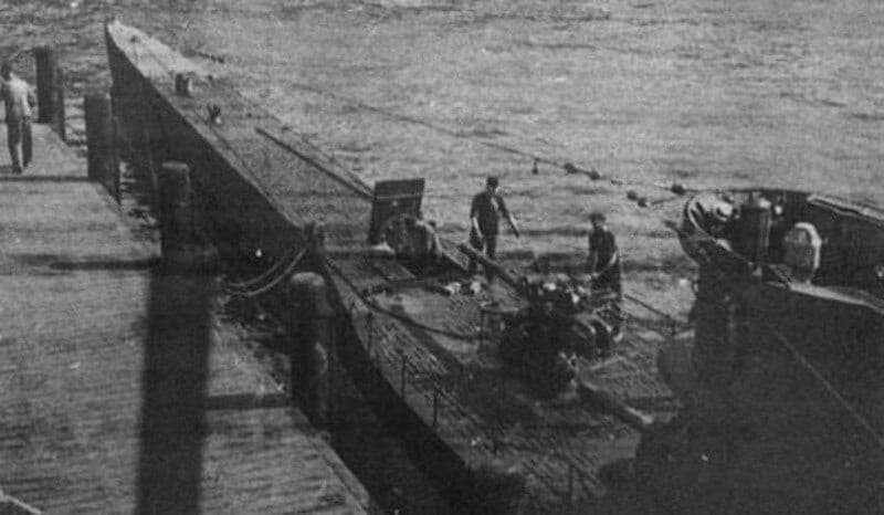 """U-576 at the dock. """"Rarely have we left port with this much confidence, and the full trust of our Admiral. This time there were no flowers decorating the boat; instead little Christmas trees adorned the bridge."""" (Photo: On combat station! U-Boat engagement against England and America by R. Hardegen, courtesy of Ed Caram Collection, via NOAA)"""