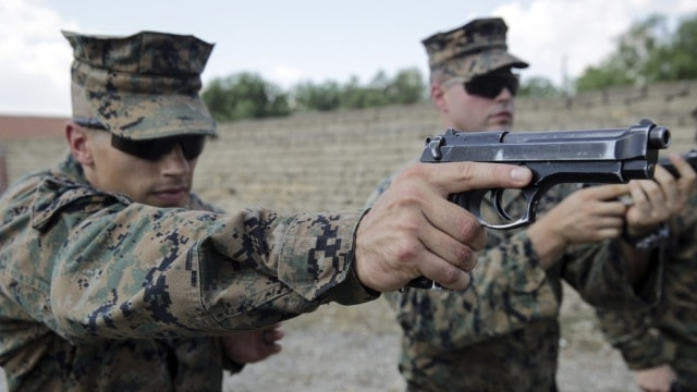 Marine Sgt. Spencer Jimick aims his M9 Beretta at a target during a live-fire range (Photo: Cpl. Alexander Mitchell/U.S. Marine Corps)