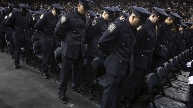 Newly inducted New York Police officers observe a solemn moment at a graduation ceremony at Madison Square Garden on Dec. 29, 2015 (Photo: Reuters)