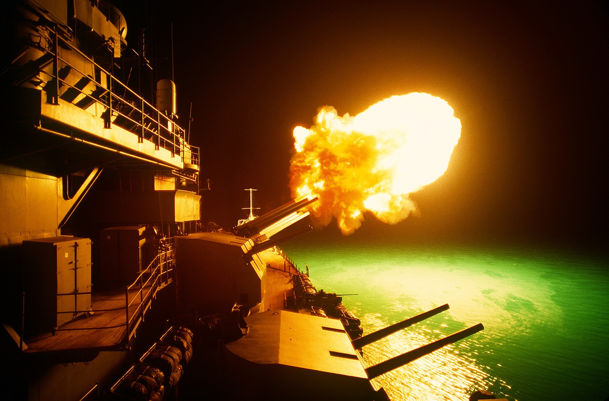 A Mark 7 16-inch/50 caliber gun is fired aboard the battleship USS MISSOURI (BB-63) as night shelling of Iraqi targets takes place along the northern Kuwaiti coast during Operation Desert Storm. (Photo: National Archives)