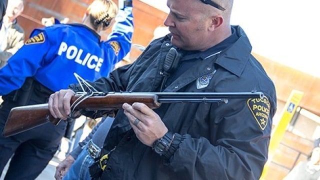 Officer Eric Coutts is checking the serial number on the rifle at the gun buyback event at the Midtown Tucson Police Department Substation on Tuesday, Jan. 8, 2012 in Tucson, Ariz. (Photo: Noelle Haro-Gomez/Tucson Weekly)