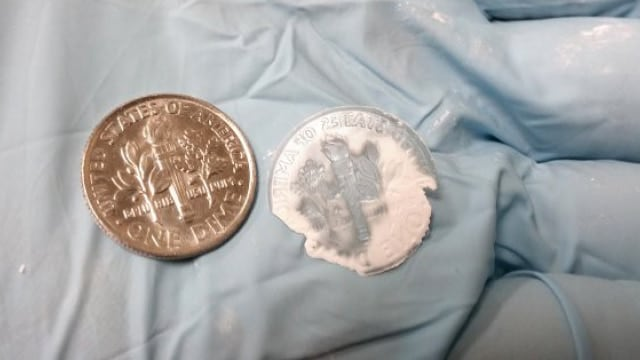 Picatinny Arsenal engineers created a glass formed amorphous explosive pellet, on right, that mimics the shape of a dime. Mission Impossible stuff here. (Photo: U.S. Army)