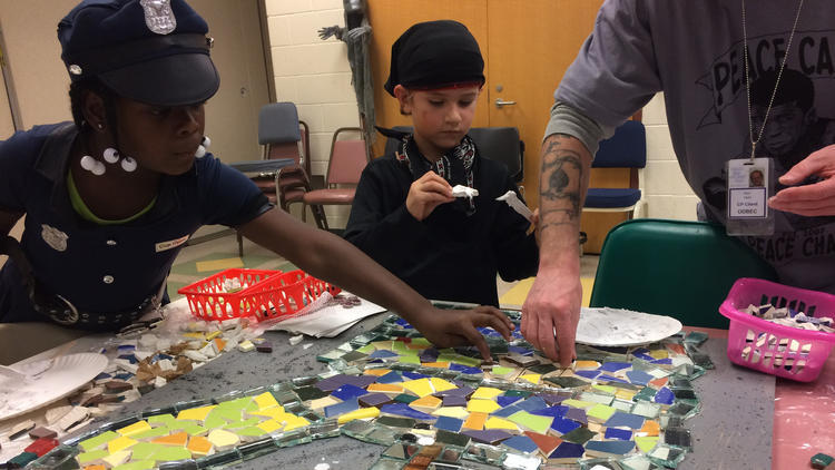 Ariyonna Pritchett, left, and Sebastian Taylor, middle, help a volunteer build a peace-themed mosaic featuring toy guns traded in for peaceful prizes. (Photo: Erin Cox / Baltimore Sun)
