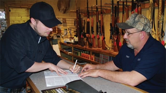 A man fills out a firearms background check form (Photo: FixNICS.com)