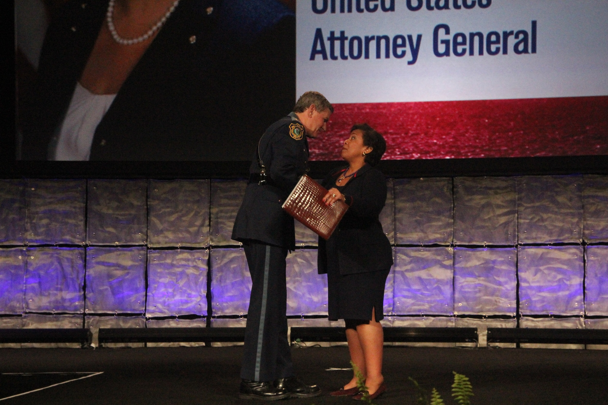 U.S. Attorney General Loretta Lynch is greeted by IACP head Terry Cunningham before taking the podium during the National Association of Police Chiefs annual convention in San Diego Oct. 15-18, 2015. (Photo: Jared Morgan / Guns.com)