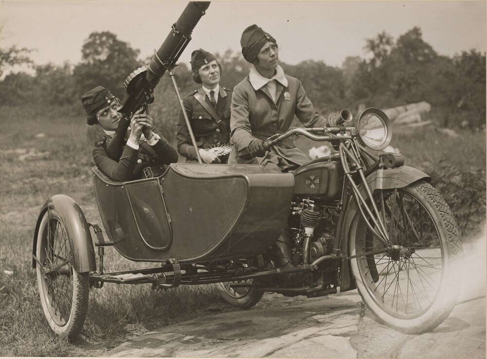 Original Caption: Women's machine gun squad police reserves of New York City. Practicing with Lewis Machine Gun which is to be sent to the front. The killing range of this gun is 2 miles and it fires 500 shots per minute. Captain Elise Reniger, manning the gun, Miss Helen M. Striffler on the rear seat, and Mrs. Ivan Farasoff driving. Date Taken: 8/1/1918 Photographer: International Film Service.