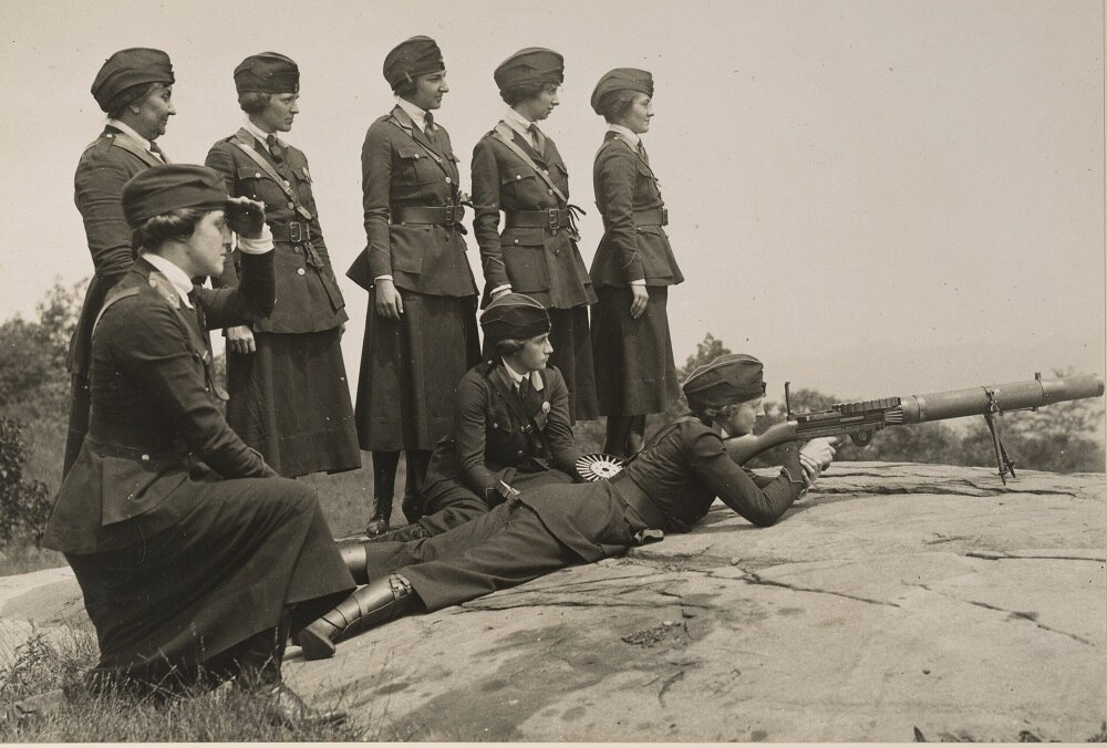 Original Caption: Women's machine gun squad police reserves, New York City. Practicing with Lewis Machine Gun which is to be sent to the front. The killing range of this gun is 2 miles and it fires 500 shots per minute. The group includes Mrs. Heydecker, Amelia Velleman, Helen M. Striffler, Leone Cuthbertson, Hazel M. Rogers, Rose B. Breler. Date Taken: 8/1/1918 Photographer: International Film Service