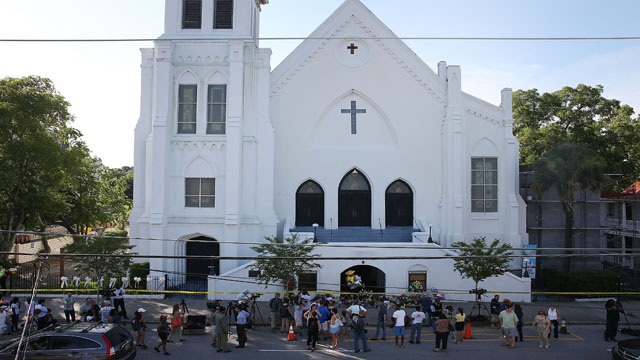 People stand outside the Emanuel AME Church after a mass shooting at the church that killed nine people on June 18, 2015, in Charleston, South Carolina. A 21-year-old suspect, Dylann Roof of Lexington, South Carolina, was arrersted Thursday during a traffic stop. Emanuel AME Church is one of the oldest in the South. (Photo: Joe Raedle/Getty Images)
