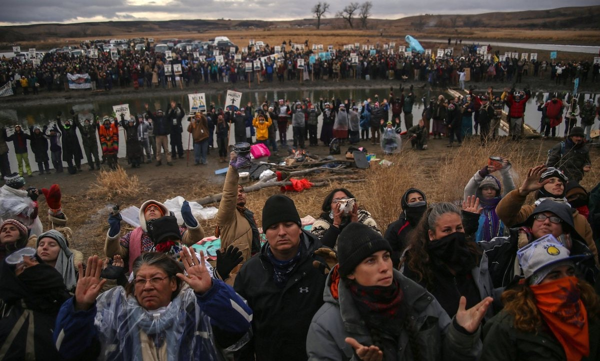 Dakota Access pipeline protestors pray at a demonstration rallying against the $3.8 billion project. (Photo by: ZUMA Wire/REX/Shutterstock)