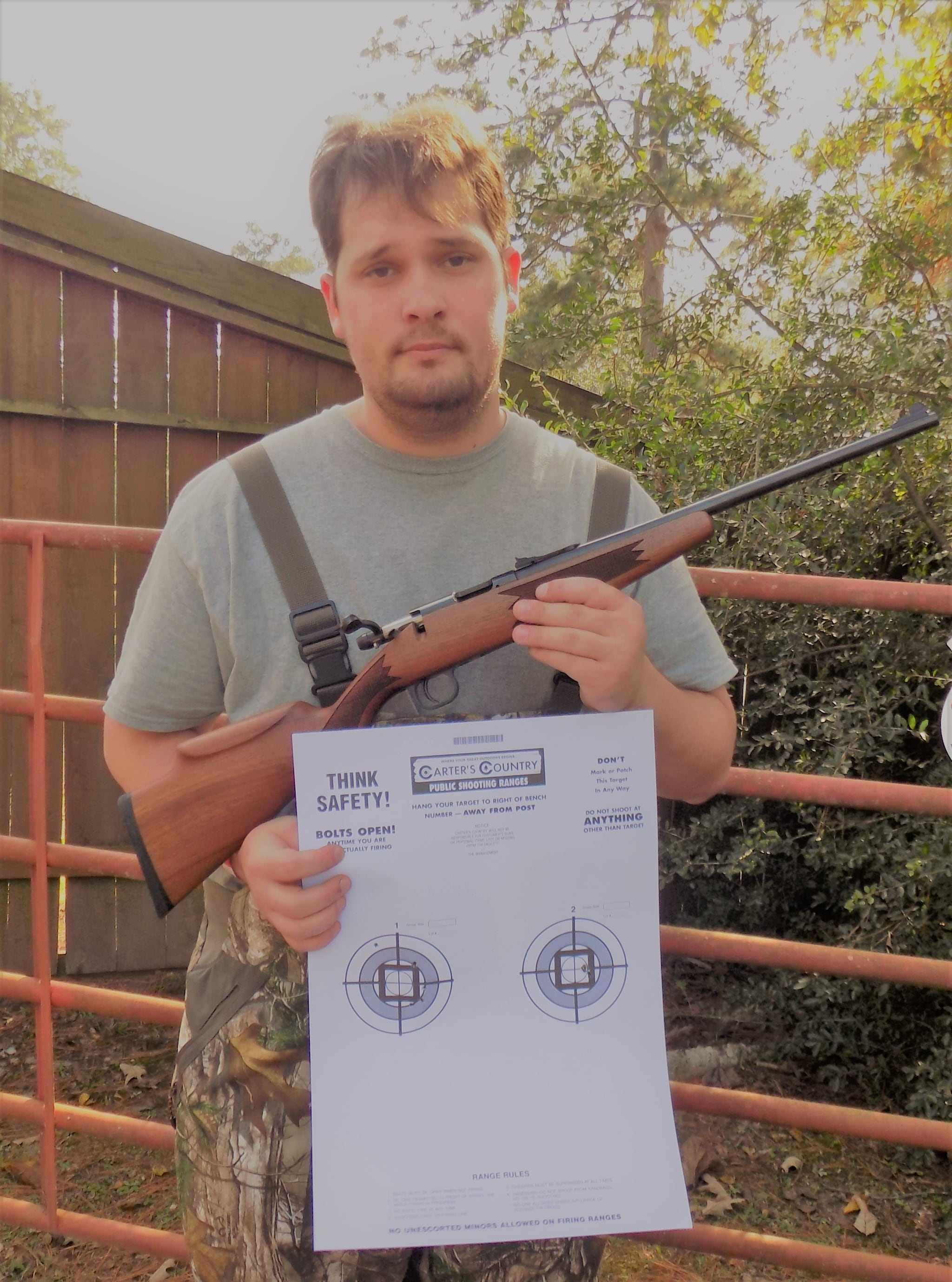 The author showing off some 25 yard groups with the Keystone rifle. Note the one hole group using Federal HV Match. The left is using Remington Golden ammo.