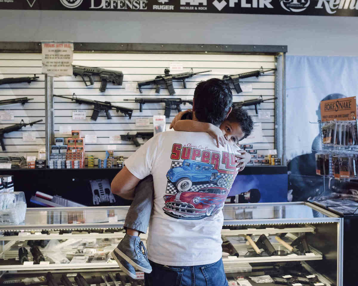 A father holds his son while checking out guns on display at Westside Armory, Las Vegas, NV (Photo: John Francis Peters)