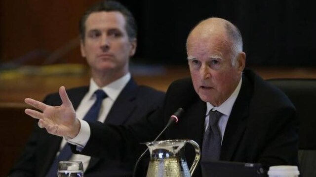 Gov. Jerry Brown, right, signed a host of new gun control bills into law only to have Lt. Gov. Gavin Newsom, left, usher through his own set of proposals via voter referendum this month. (Photo: Eric Risberg/ The Associated Press)