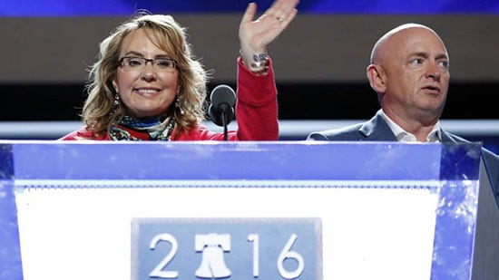 Former Rep. Gabby Giffords, D-Ariz, waves from the podium as her husband Astronaut Mark Kelly (ret.) looks on during a sound check before the start of the first day session of the Democratic National Convention in Philadelphia, Monday, July 25, 2016 (AP Photo/Carolyn Kaster)
